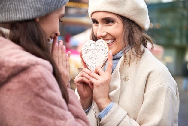 Mulher segurando um pão de mel em formato de coração Foto gratuita