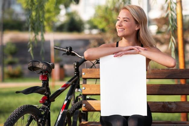 Mulher segurando um papel branco de cópia espaço no parque Foto Premium