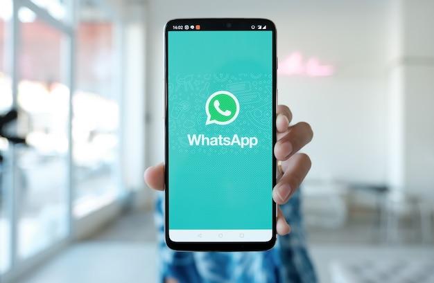 Mulher segurando um smartphone e appstore aberto pesquisando serviço de internet social whatsapp na tela. Foto Premium
