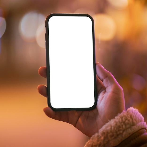 Mulher segurando um smartphone em branco com efeito bokeh ao redor Foto gratuita