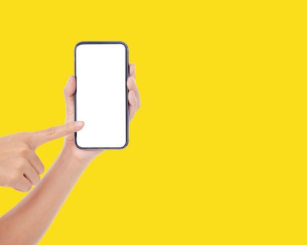 Mulher segurando um telefone celular com uma tela em branco na parede amarela, close-up Foto Premium