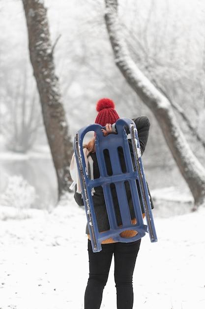 Mulher segurando um trenó ao ar livre Foto gratuita