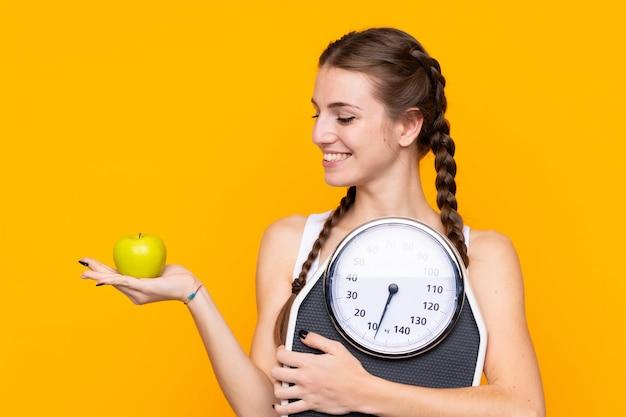 Mulher segurando uma balança sobre parede amarela Foto Premium