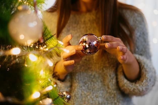 Mulher segurando uma bola de árvore de natal Foto gratuita