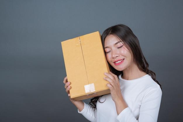 Mulher segurando uma caixa de correio marrom made gestos com linguagem gestual. Foto gratuita