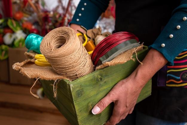 Mulher segurando uma caixa de madeira com ferramentas em uma floricultura Foto Premium