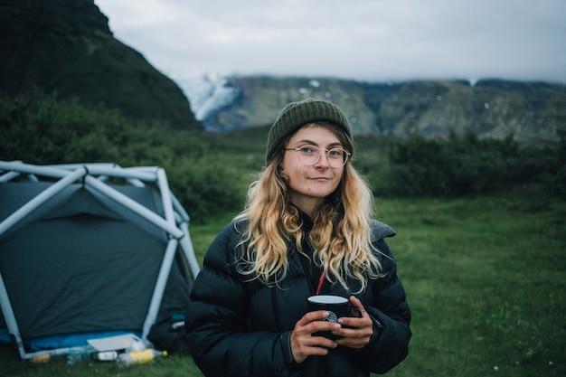 Mulher segurando uma caneca de acampamento em uma viagem de caminhada na islândia Foto gratuita