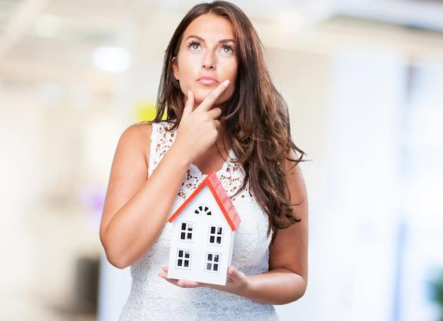 Mulher segurando uma casa e pensar em algo Foto gratuita