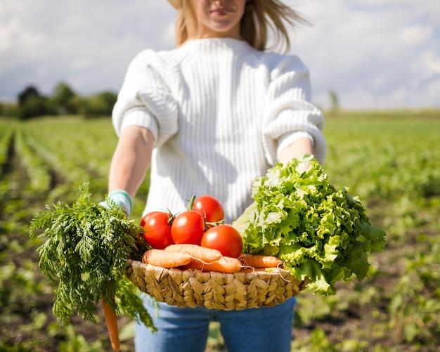 Mulher segurando uma cesta cheia de legumes na frente dela Foto gratuita