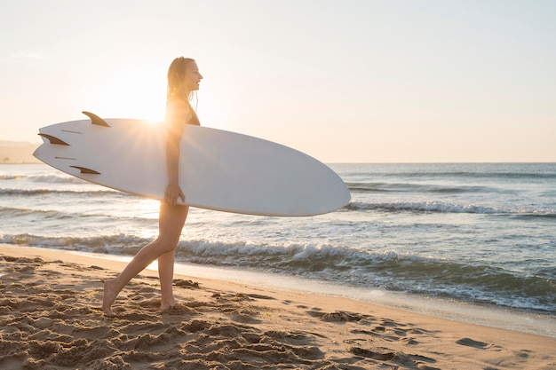 Mulher segurando uma prancha de surf Foto gratuita