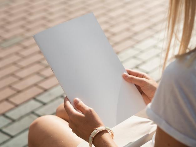 Mulher segurando uma revista de maquete Foto gratuita