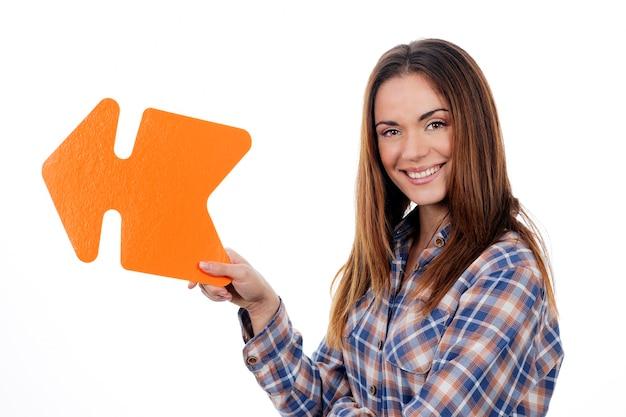 Mulher segurando uma seta laranja isolada no fundo branco Foto gratuita