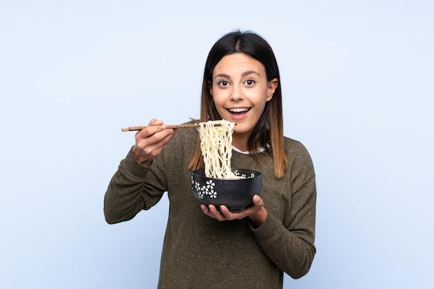 Mulher segurando uma tigela de macarrão com pauzinhos e comê-lo Foto Premium