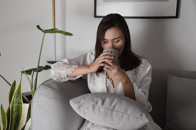Mulher segurando uma xícara de café à noite, sentada em um sofá na sala de estar de casa Foto Premium