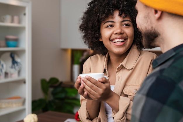 Mulher segurando uma xícara de café e olhando para o namorado Foto gratuita