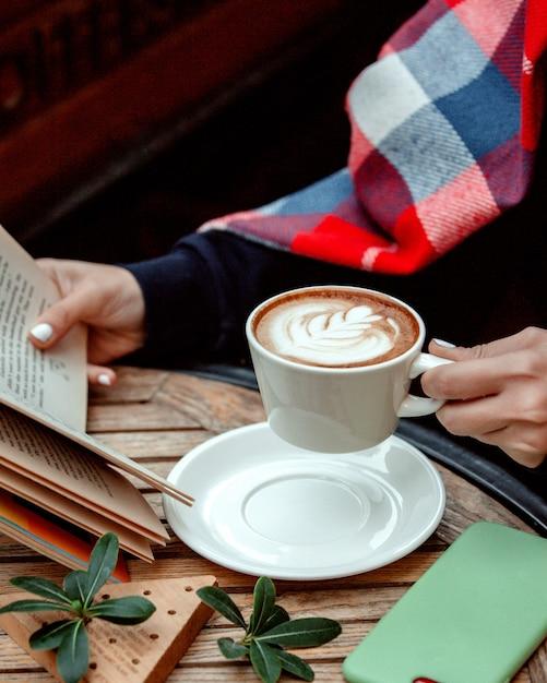 Mulher segurando uma xícara de cappuccino e lendo um livro Foto gratuita