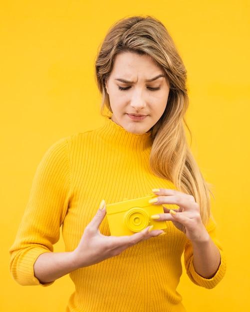 Mulher segurando velha câmera amarela Foto gratuita