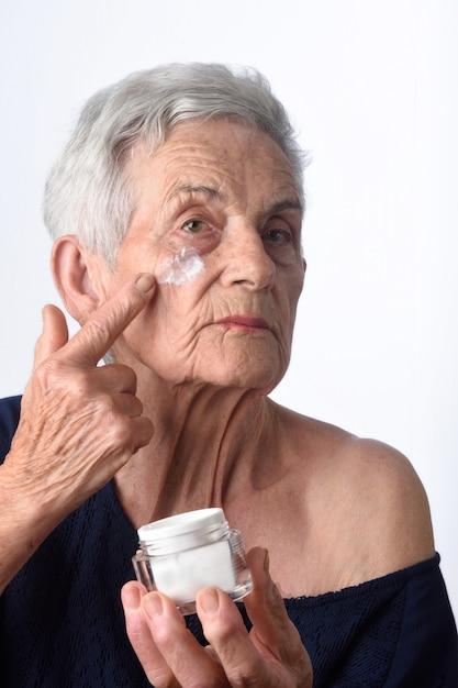 Mulher sênior, aplicando, creme pele, ou, moisturizer, para, dela, rosto Foto Premium