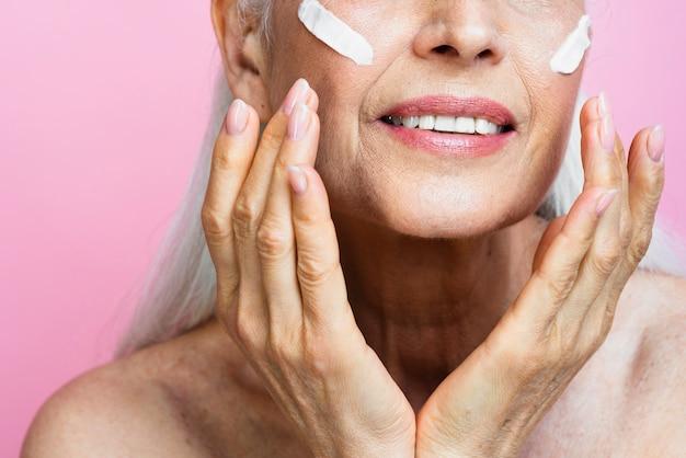 Mulher sênior, aplicar cuidados com a pele no rosto Foto gratuita