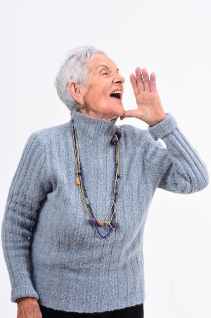 Mulher sênior, colocando a mão na boca e está gritando no fundo branco Foto Premium