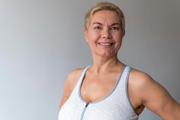 Mulher sênior com cabelo curto fazendo exercícios Foto gratuita