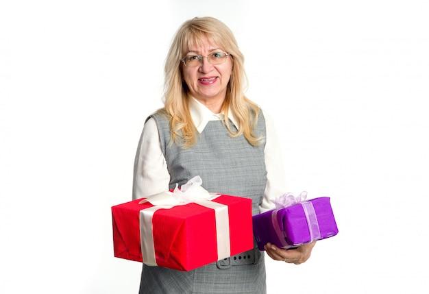 Mulher sênior com caixas de presentes nas mãos dela sobre um fundo claro. Foto Premium