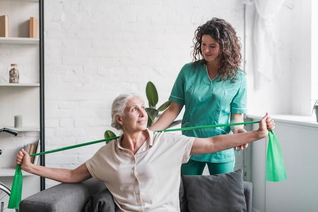 Mulher sênior, com, faixa estiramento, sendo, assistência, por, femininas, fisioterapeuta Foto gratuita