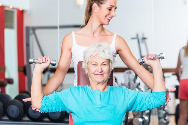Mulher sênior, com, treinador, em, ginásio, levantamento, dumbbell Foto Premium