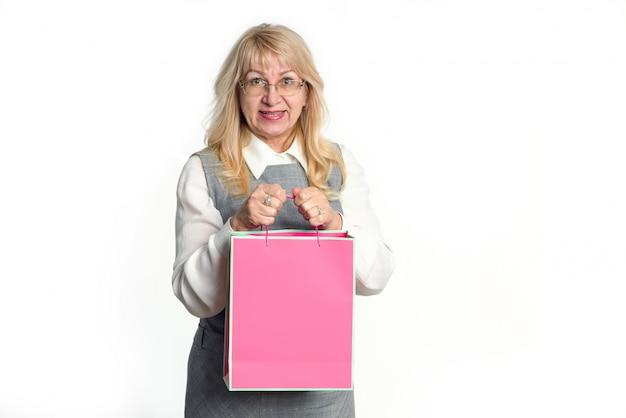 Mulher sênior com um pacote rosa sobre fundo branco. Foto Premium