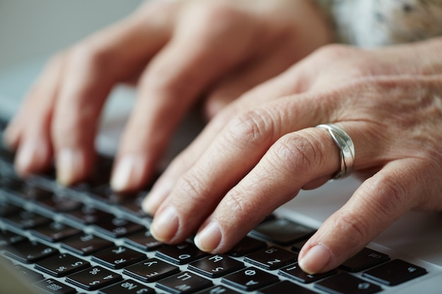 Mulher sênior digitando no teclado Foto gratuita