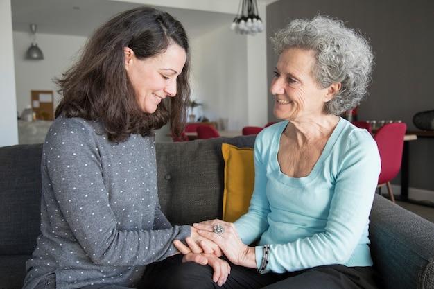 Mulher sênior e filha conversando em casa Foto gratuita