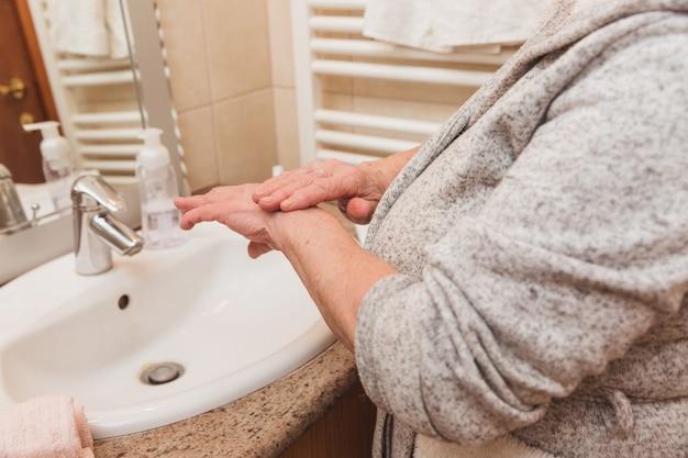 Mulher sênior, em, bathrobe, aplicando creme mão, em, banheiro Foto Premium