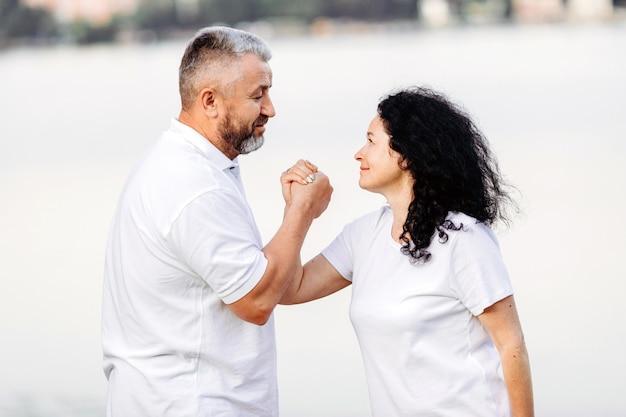 Mulher sênior feliz e homem sênior tomando exercício queda de braço, olhando um ao outro. esporte Foto Premium