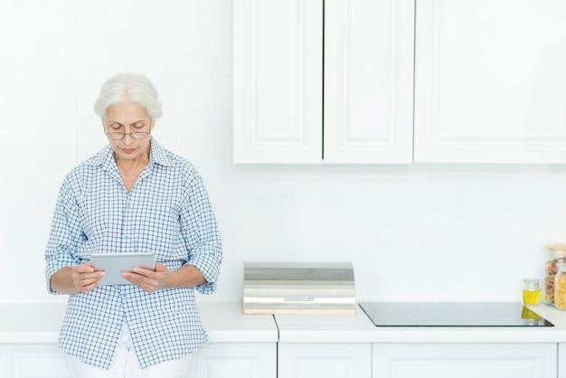 Mulher sênior, ficar, em, cozinha, usando, tablete digital Foto gratuita
