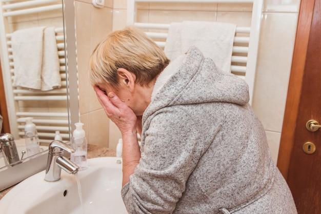 Mulher sênior, lavar o rosto em casa Foto Premium