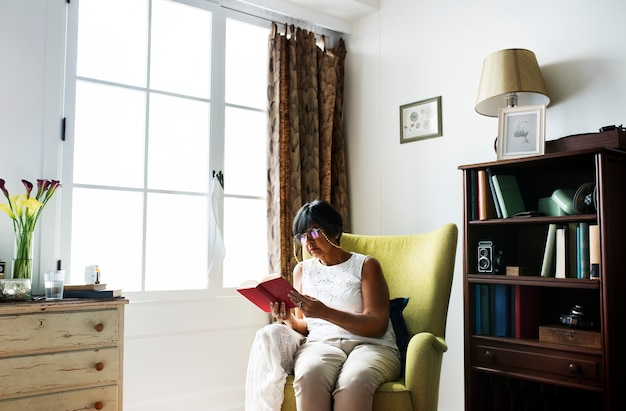 Mulher sênior, livro leitura, em, a, sala Foto Premium