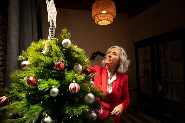 Mulher sênior, montando, árvore natal Foto gratuita