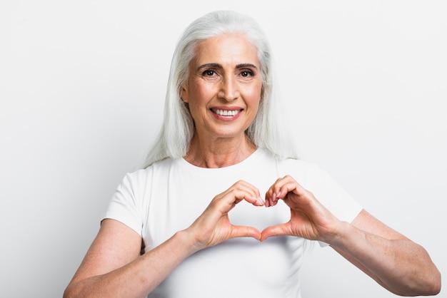 Mulher sênior, mostrando, sinais amor Foto gratuita