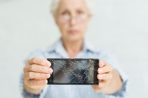 Mulher sênior, mostrando, smartphone, com, tela rachada Foto gratuita
