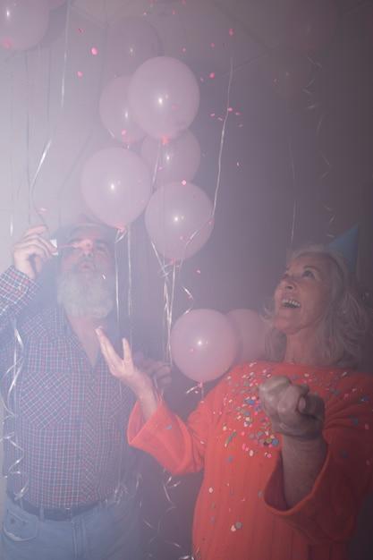 Mulher sênior, olhar, dela, marido, soprando, bolhas sabão, em, partido aniversário Foto gratuita
