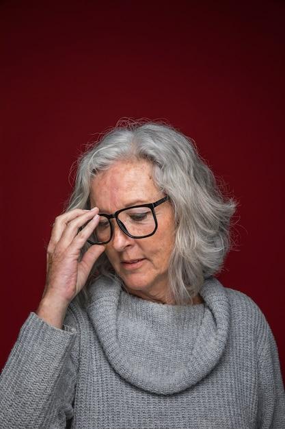 Mulher sênior, pôr óculos, ligado, dela, rosto, contra, colorido, fundo Foto gratuita