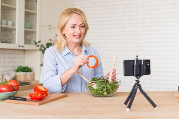 Mulher sênior que faz a chamada de vídeo no celular mostrando a fatia de pimentão ao preparar a salada Foto gratuita