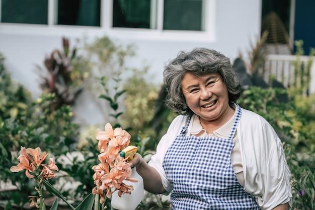 Mulher sênior, reunião, flores, em, jardim Foto gratuita