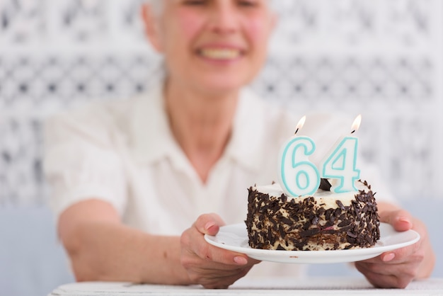 Mulher sênior, segurando, prato, de, bolo aniversário delicioso, com, glowing, numere velas Foto gratuita