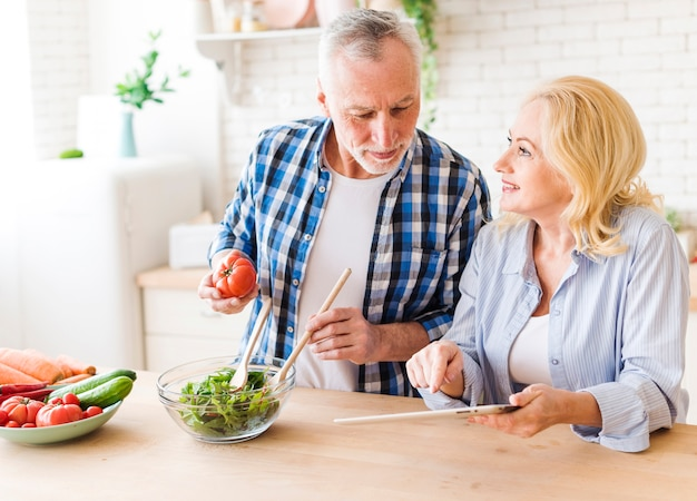 Mulher sênior, segurando, tablete digital, em, mão, mostrando, receita, para, dela, marido, preparar, a, salada, cozinha Foto gratuita