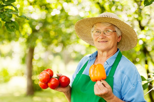 Mulher sênior segurando tomates e pimentão amarelo Foto gratuita
