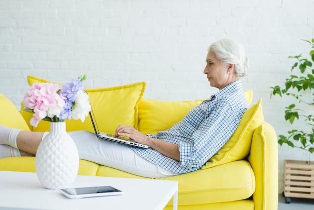 Mulher sênior, sentar sofá, usando computador portátil Foto gratuita