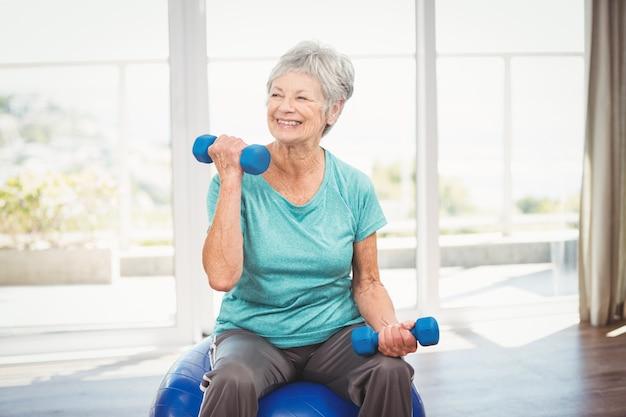 Mulher senior sorridente segurando halteres Foto Premium