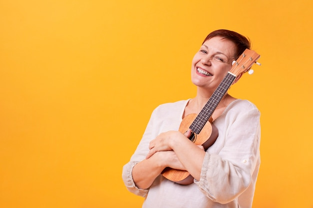 Mulher senior sorridente segurando ukulele Foto gratuita