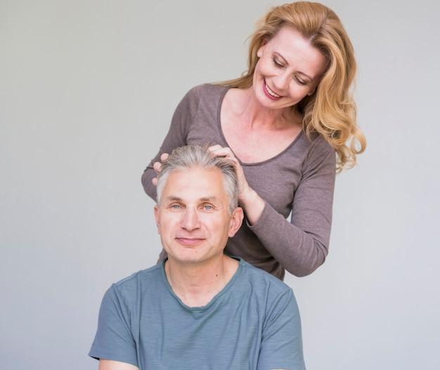 Mulher senior sorridente, tocando o cabelo de maridos Foto gratuita